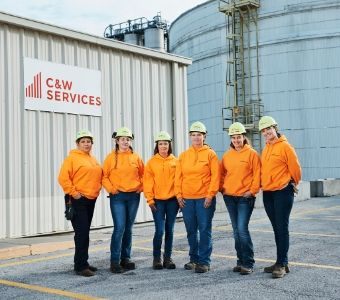 A team of female maintenance workers pose for a photo outside of a site in Nebraska